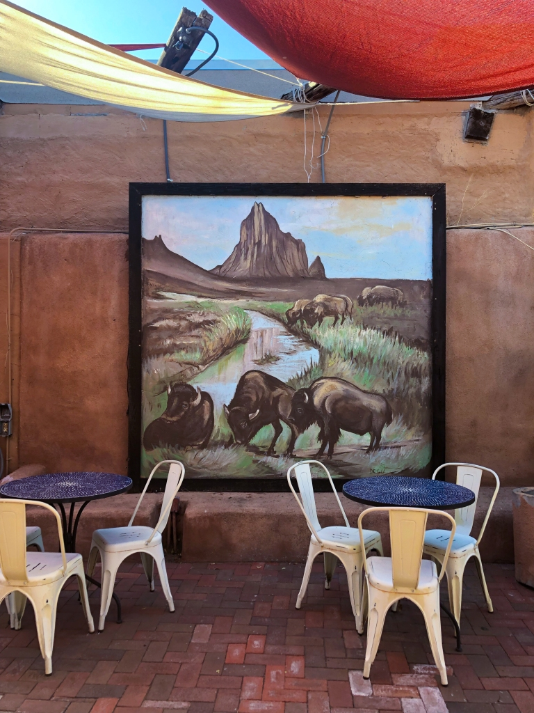 outdoor seating area in Albuquerque, NM with a painting of Bison grazing in the background