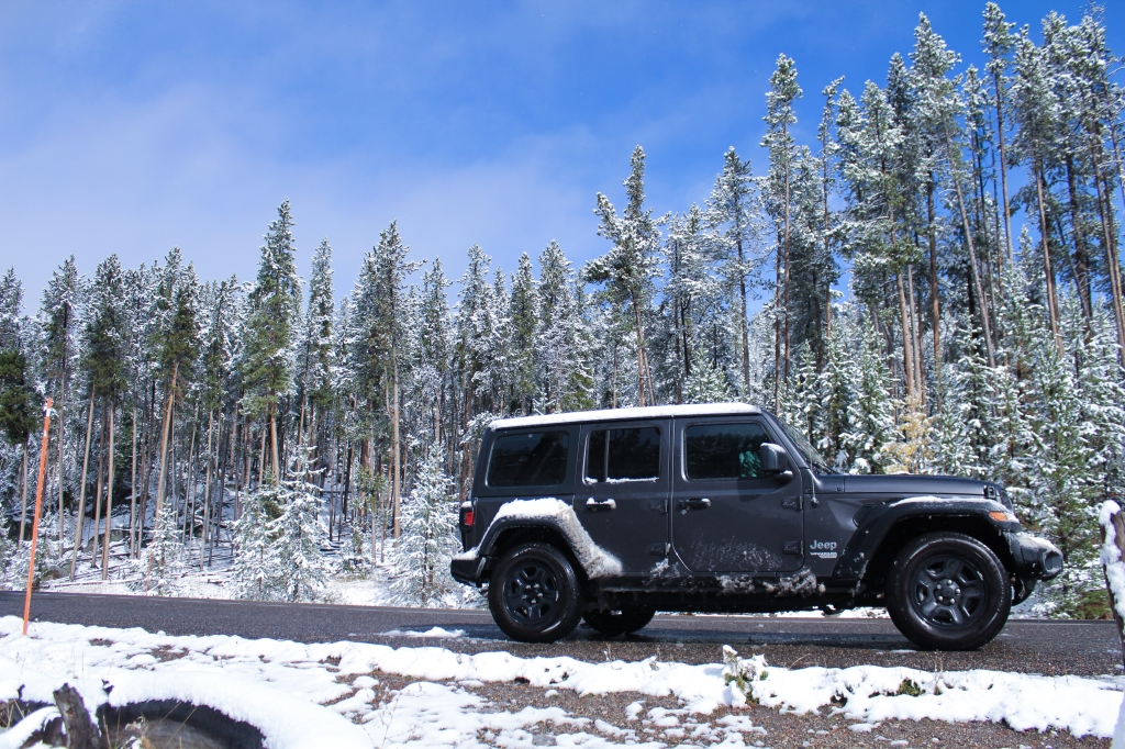 2018 Jeep Wrangler on the side of the road with blue sky and snow covered trees in background