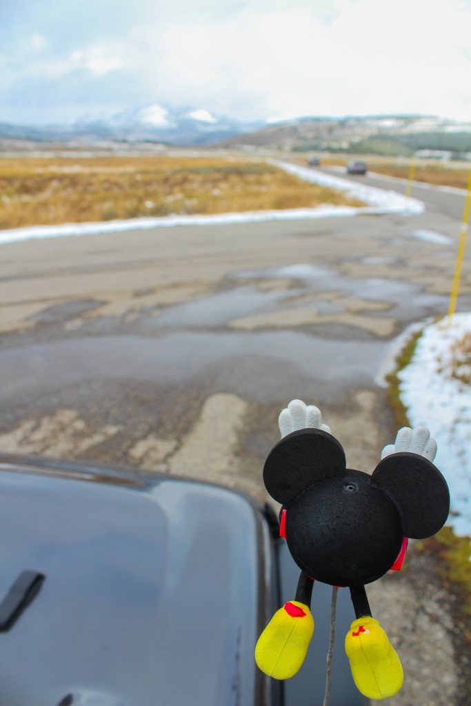 The hood of a gray 2018 Jeep Wrangler Unlimited Sport can be seen. In the forefront of the image is a mickey mouse antenna topper in the superman position. In the background of the photo is a road with two blurry cars and a snow covered mountain peak in the distance.