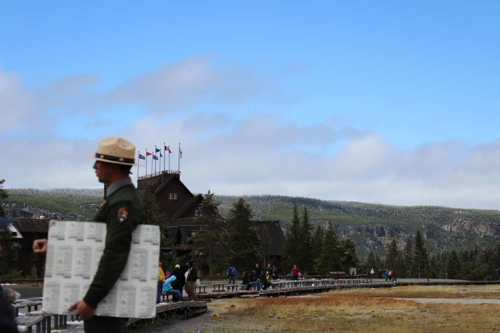 image of a park ranger holding a poster board in front of the old faithful inn