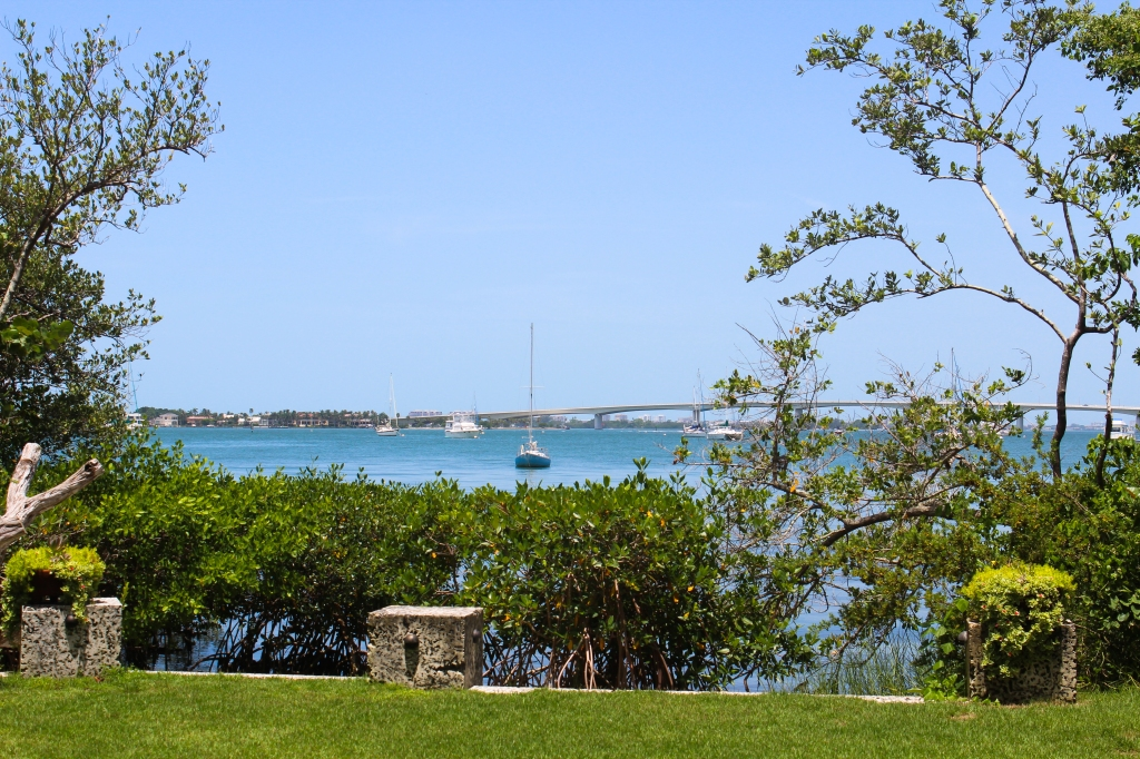 View of the bay from inside Marie Selby Botanical Garden with boats and a bridge in the background
