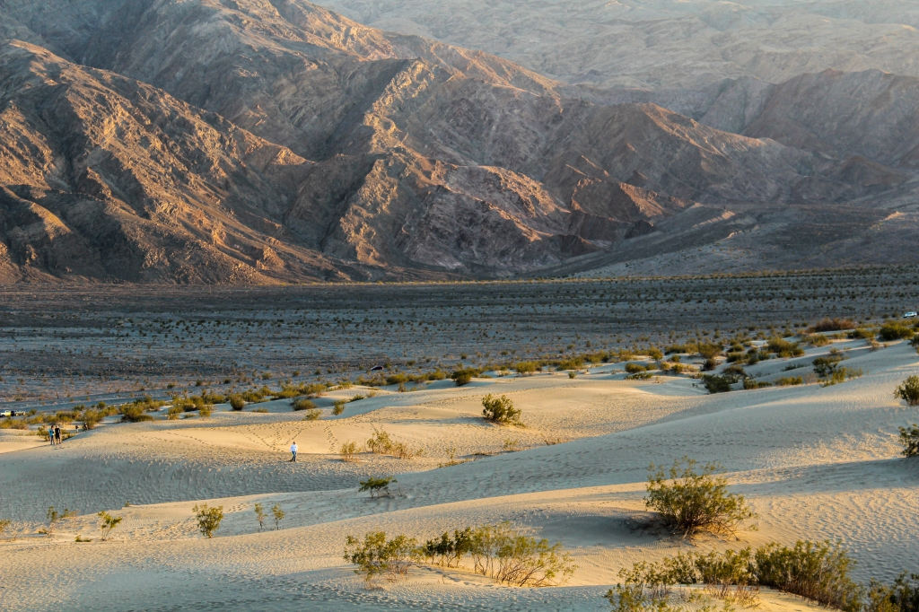 Sunset at the Mesquite Flat Sand Dunes, image of the sand dunes meeting the mountains with a person in middle ground wandering